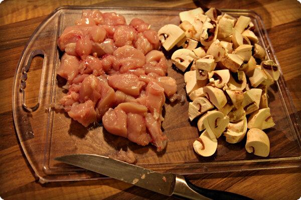 Курицу режем порционно, но не маленьких размеров, чтобы мясо было более сочным. У шампиньонов оставляем только шляпки ..